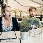 Trötta och förvånade ansikten vid middagsbordet på restaurang